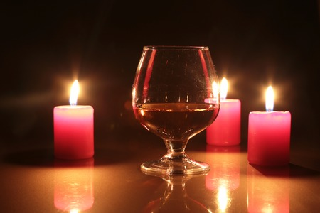 Glass of brandy or cognac and candle on the wooden table. Stock Photo