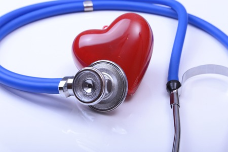 Cardiogram with stethoscope and red heart on table, closeup.