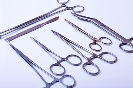 forceps: surgical instruments and tools including scalpels, forceps and tweezers arranged on a table for a surgery.