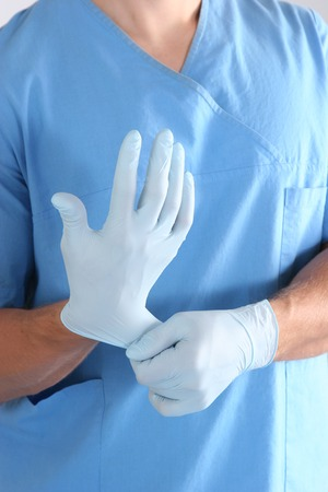 sterile: Doctor putting on sterile gloves isolated white