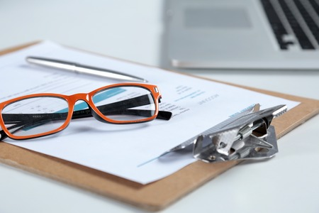 Closeup of white desktop with laptop, glasses, coffee cup, notepads and other items on blurry city background