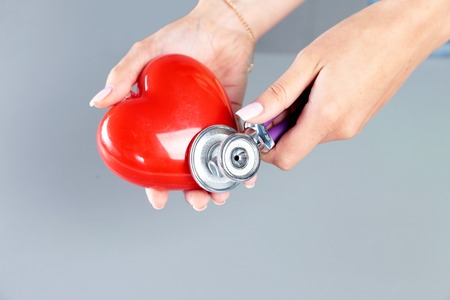 Female medicine doctor hold in hands red toy heart and stethoscope head. Cardio therapeutist, student education, physician make cardiac physical, rate measure, arrhythmia concept Stock Photo