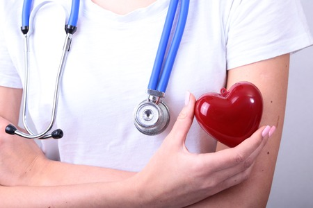 myocardium: Female medicine doctor hold in hands red toy heart and stethoscope head. Cardio therapeutist, student education, physician make cardiac physical, rate measure, arrhythmia concept Stock Photo