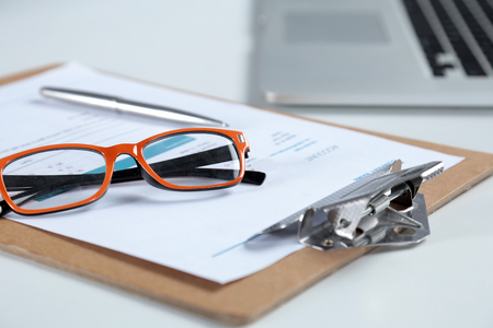 sulight: Closeup of white desktop with laptop, glasses, coffee cup, notepads and other items on blurry city background