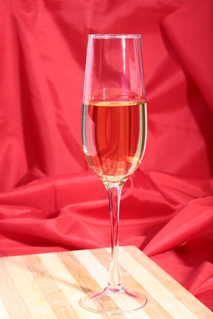 Glass of white wine on red background