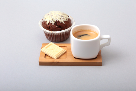 Classic espresso in white cup with cake and chocolate on white background.