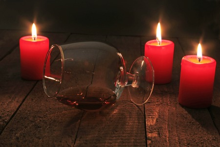 snifter: Glass of brandy or cognac and candle on the wooden table. Celebration composition.