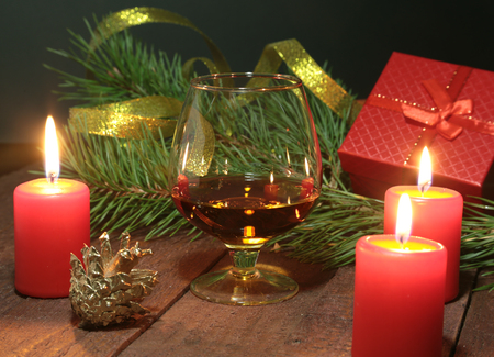 Glass of brandy or cognac, gift box and candle on the wooden table. Celebration composition.