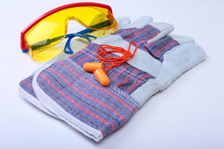 Orange earplug, safety glasses and glovs. Earplug to reduce noise on a white background .