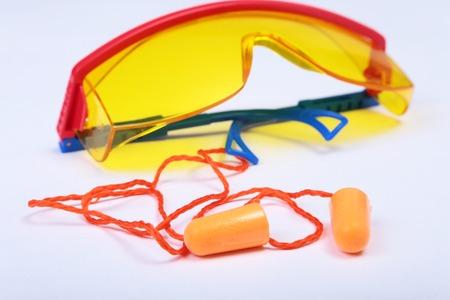 Orange earplug and safety glasses. Earplug to reduce noise on a white background . Stock Photo