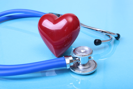Medical stethoscope and red heart isolated on blue mirror background. you can place your text.