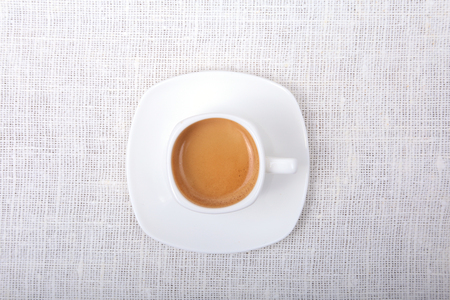Classic espresso coffee in white cup isolated on white background. Top View. Stock Photo