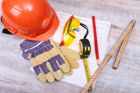 claw hammer: Orange hard hat, safety glasses, gloves, pen and measuring tape on wooden background. Stock Photo