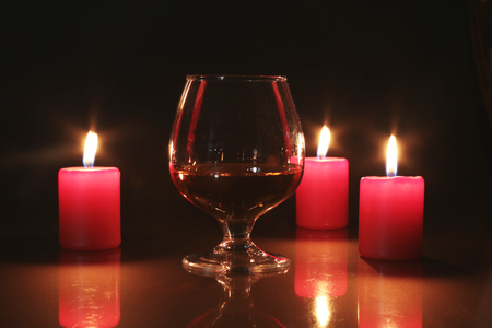 Glass of brandy or cognac and candle on the wooden table