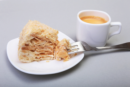 Homemade Napoleon puff cake on plate and traditional espresso coffee isolated on white background. close-up.