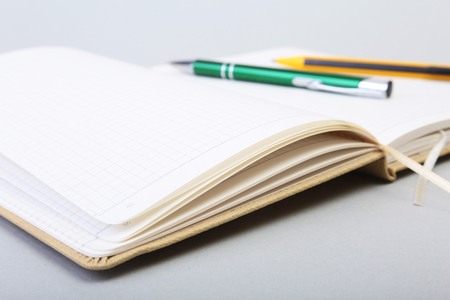 Open Blank Page notebook and pen on white table.