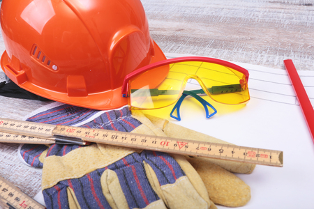 claw hammer: Orange hard hat, safety glasses, gloves and measuring tape on wooden background.