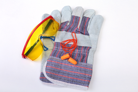 Orange earplug, safety glasses and gloves for work. Earplug to reduce noise on a white background.