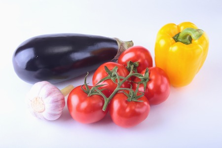 Fresh assorted vegetables eggplant, bell pepper, tomato, garlic. Isolated on white background. Selective focus. Stock Photo