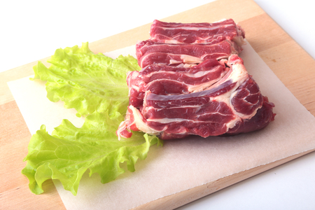 Raw beef edges and lettuce leaf on wooden desk isolated on white background from above and copy space. ready for cooking