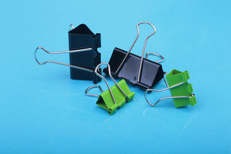 Close-up with Set of color clerical clips for paper on blue background.