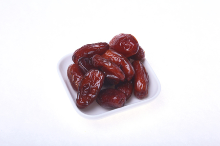 Delicious dried organic dates on bowl isolated over white background.