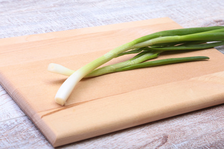 Small bundle of washed fresh green onions with long stems and tiny roots on wood table.