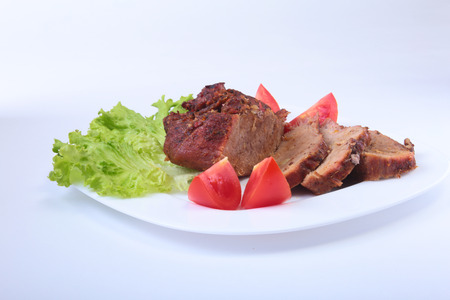 Steak of grilled meat with tomato, lettuce and beans pomegranate on white plate. Stock Photo
