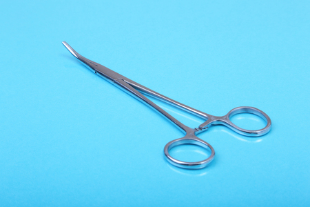 Close Up Surgical instruments and tools on blue mirror background. Selective focus. Stock Photo