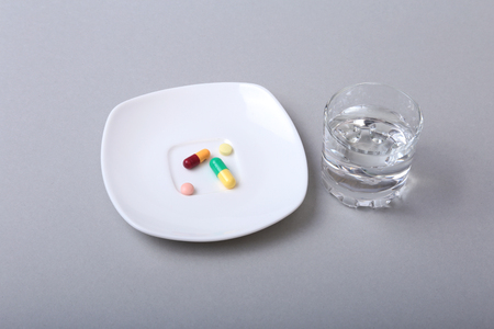 effervescence: Glass of water and pills on white background