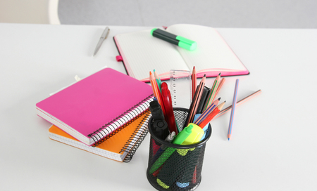 Closeup of white desktop with notepads, pen and other items. Selective focus.