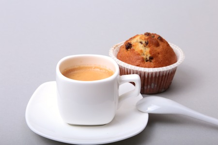 Classic espresso in white cup with homemade cake and chocolate on white background.