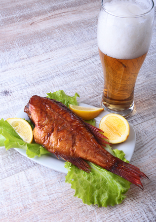 prepared: Smoked fish and lemon on green lettuce leaves on Wooden cutting board and glass with beer isolated on white background.