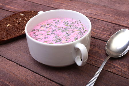 Popular spring cold soup okroshka with yoghurt. Okroshka in a bowl and slices bread on wooden table. Selective focus Фото со стока