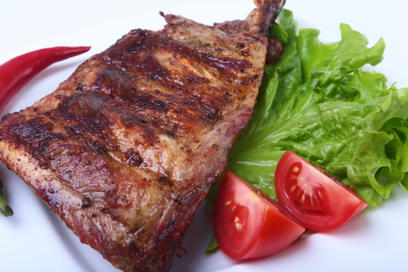 Pork ribs on grill and chili pepper with tomato, lettuce leaves on white plate