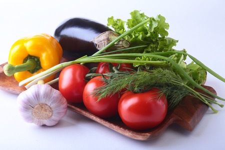 Fresh assorted vegetables, eggplant, bell pepper, tomato, garlic with leaf lettuce. Isolated on white background. Selective focus.