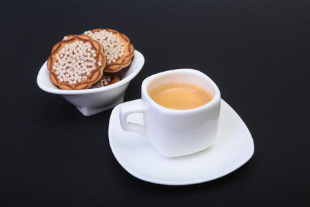 Classic espresso in white cup with homemade cake on black background. Selective focus