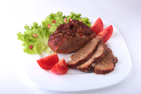 Steak of grilled meat with tomato, lettuce and beans pomegranate on white plate