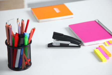 Closeup of white desktop with notepads, pen, coffee cup and other items. Selective focus.