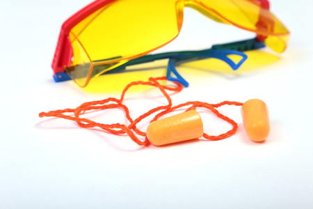 industrial noise: Orange earplug and safety glasses for work. Earplug to reduce noise on a white background .