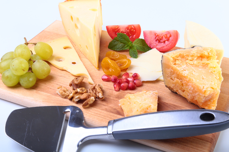 roquefort: Assortment of cheese with fruits, grapes, nuts and cheese knife on a wooden serving tray.