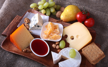 roquefort: Assortment of cheese with fruits, grapes and nuts on a wooden serving tray.