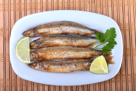Deep frying small fish capelin and sliced lemon on white plate. Good snack to beer. Stock Photo