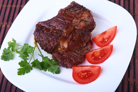 Grilled beef steak with tomato, and hot asian chillies garlic sauce on plate on wooden background.