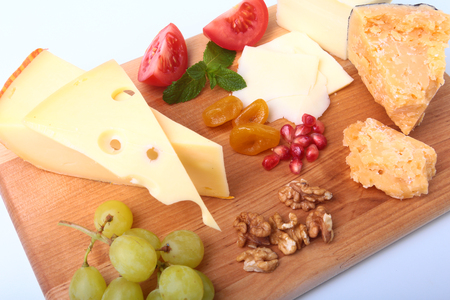 Assortment of cheese with fruits, grapes, nuts and cheese knife on a wooden serving tray.