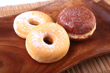 croatian: Assorted Homemade Doughnuts with Jelly filled and powdered sugar on wooden salver. Selective focus. Stock Photo