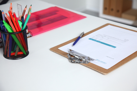 Closeup of white desktop with notepads, pen and other items. Selective focus