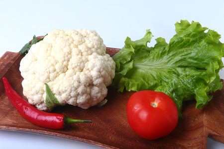 cutouts: fresh cauliflower, tomato, salad leaves and other vegetables on wooden board. Ready for cooking. Vegetarian food. Stock Photo