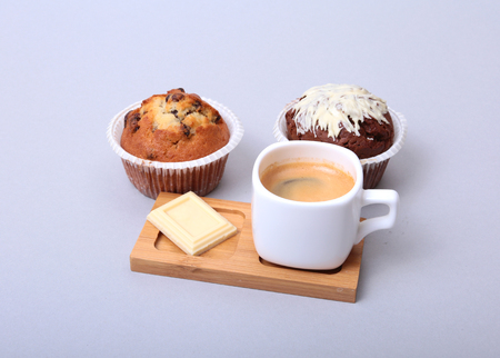 Classic espresso in white cup with homemade cake and chocolate on white background