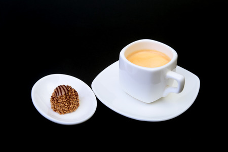 White cup of classic espresso coffee and pralines on black background.